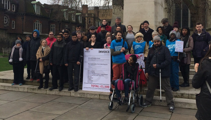 Image shows campaigners with giant invoice prop next to Houses of Parliament