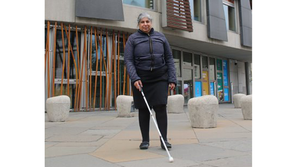 Lady using a white cane and walking down the street
