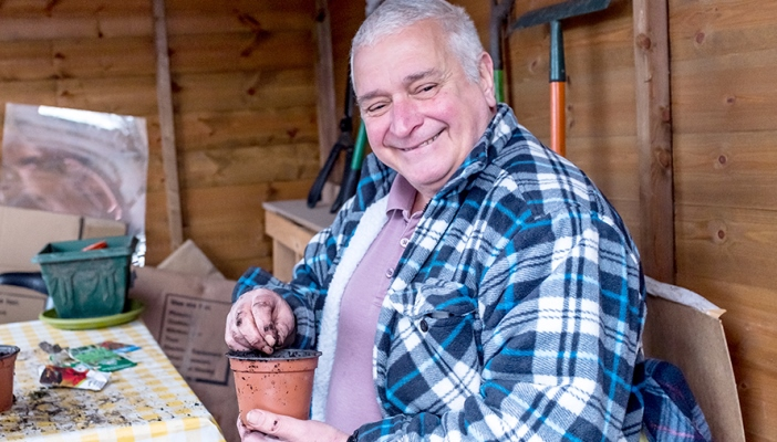 Kevin sitting in his shed, smiling and filling a plant pot with soil.