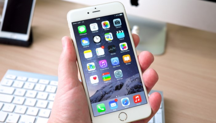 Image shows the iphone 6 in someones hand unlocked, with an Apple Mac in the background