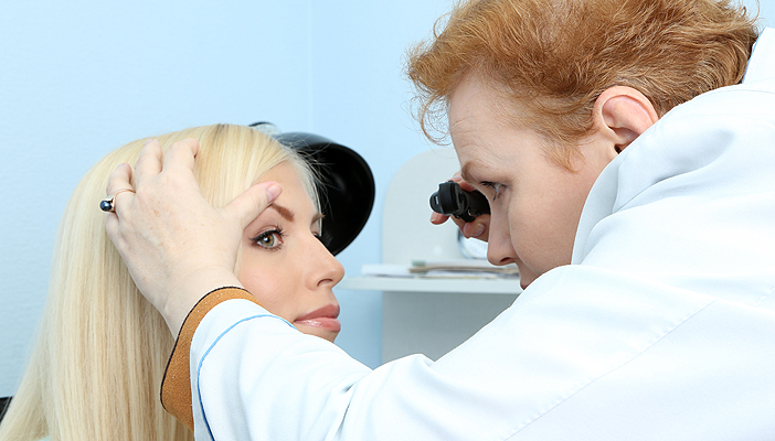 An optometrist holds the eye of a patient open during an eye examination