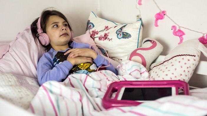 Image shows Lily-Grace lying on her bed, wearing headphones and listening to a Talking Book through an iPad