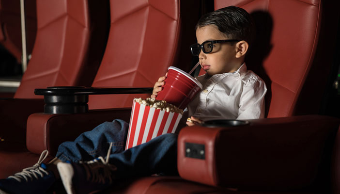 Image shows a child sat on a seat in the cinema with popcorn in his lap and wearing 3D glasses