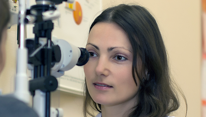 Woman at an optometrists having her retina examined