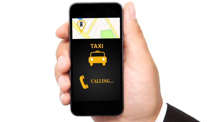 Someone holding a phone showing a taxi app