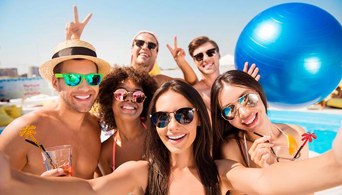 A group of people taking a selfie by a swimming pool and all wearing sunglasses