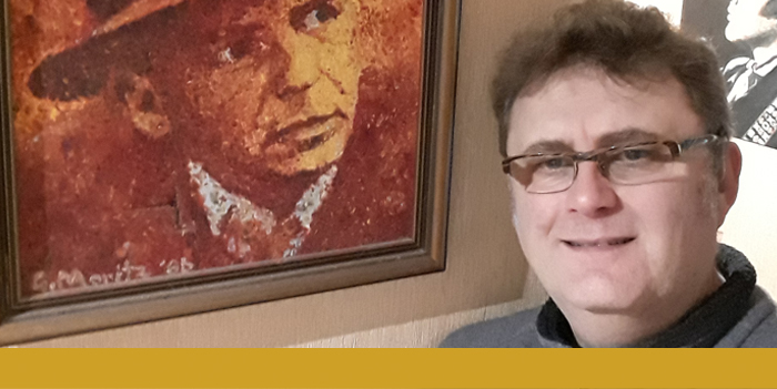 Gary Moritz stands to the right of his painting of Frank Sinatra