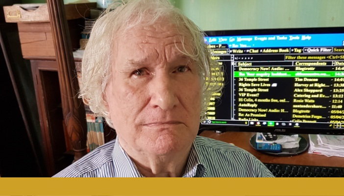 Colin Bennett sat in front of his computer looking at the camera. A gold bar spans beneath the photo