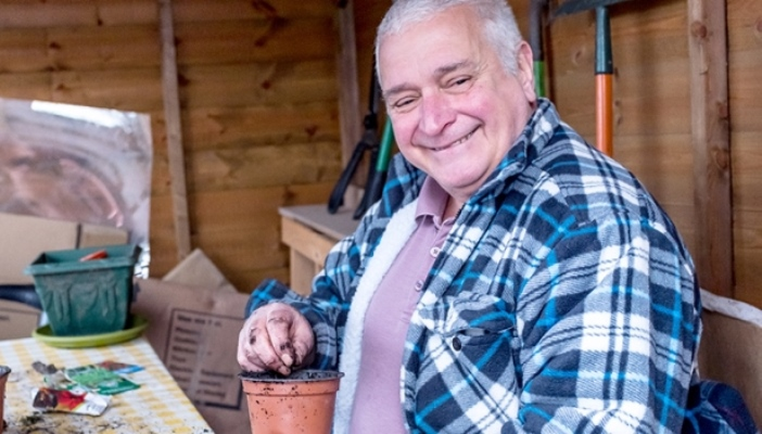 Kevin sitting in his shed, smiling and filling a plant pot