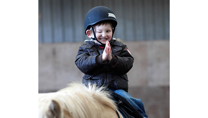 Boy clapping whilst sat on horseback