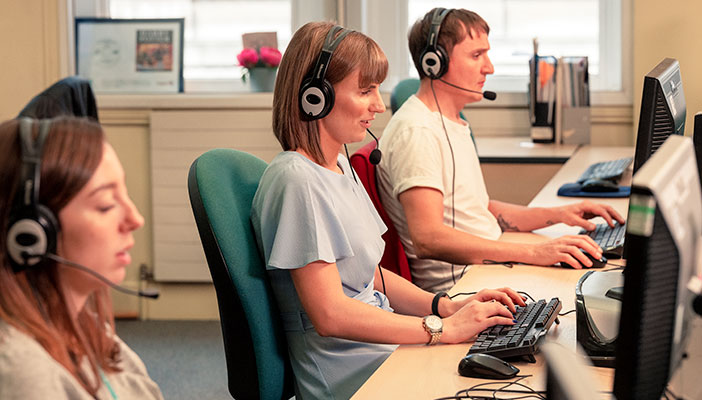 Three Helpline advisers with headsets in front of computer screens
