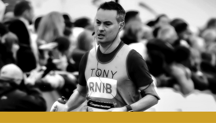 Black and white image of Anthony Pinkham running wearing RNIB running vest. A gold bar spans below the photo.