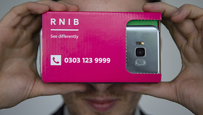 Smartphone in a cardboard RNIB Eyeware viewer held in front of a person's face