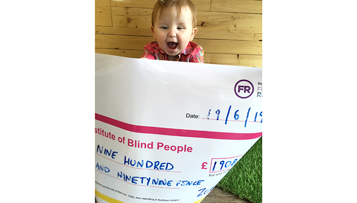 Zoe Stinson's son Harley holding a cheque for the money she raised for RNIB NI