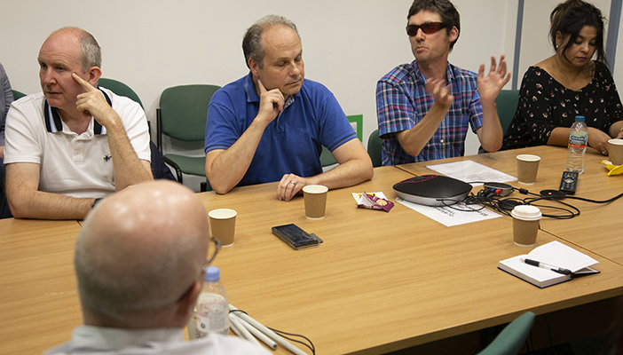 Four male and one female blind or partially sighted participant engaged in a discussion around a table.