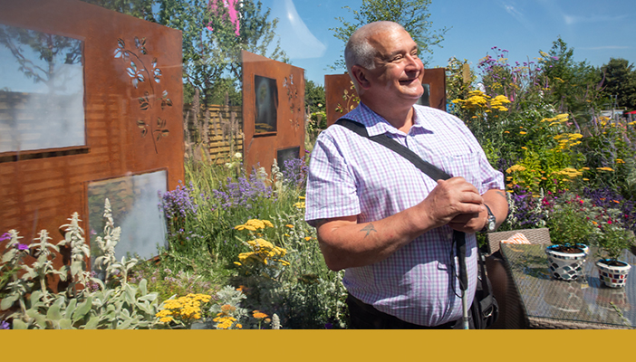 Kevin Smith in RNIB's Community Garden at RHS Flower Show 2018. A gold bar spans across the bottom of the photo