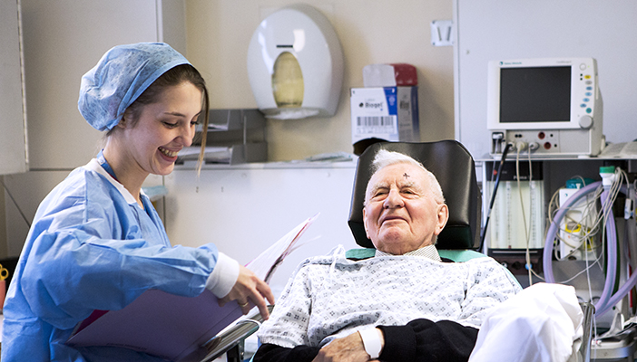 Male patient before cataract surgery in hospital talking to smiling nurse