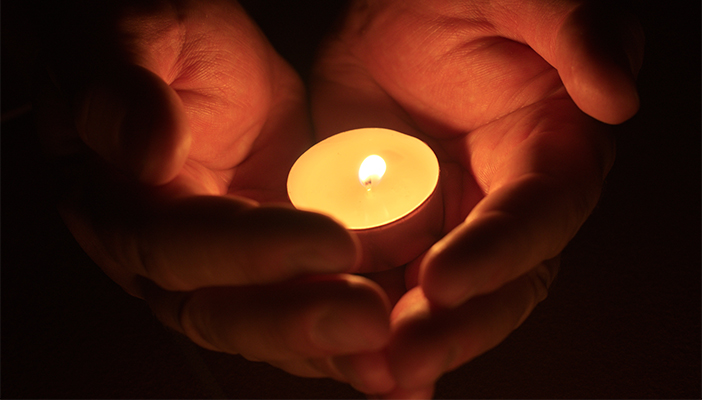 Image shows a tealight being held in someone's hand