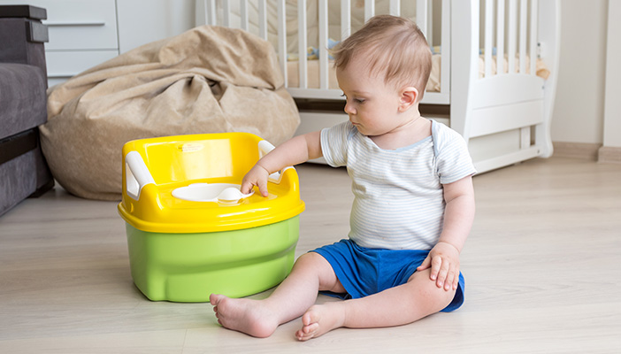 Image shows a child sitting next to and touching a potty
