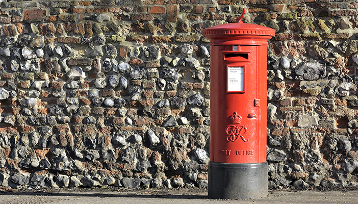 Photo of a red UK post box in front of a brick wall