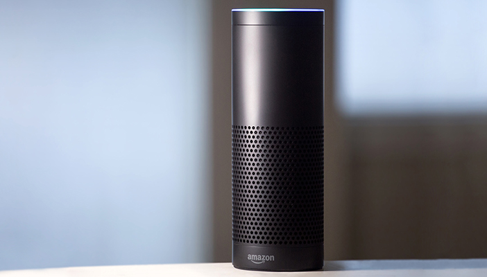 Image shows the Amazon Echo - a long black cylinder shaped gadget.
