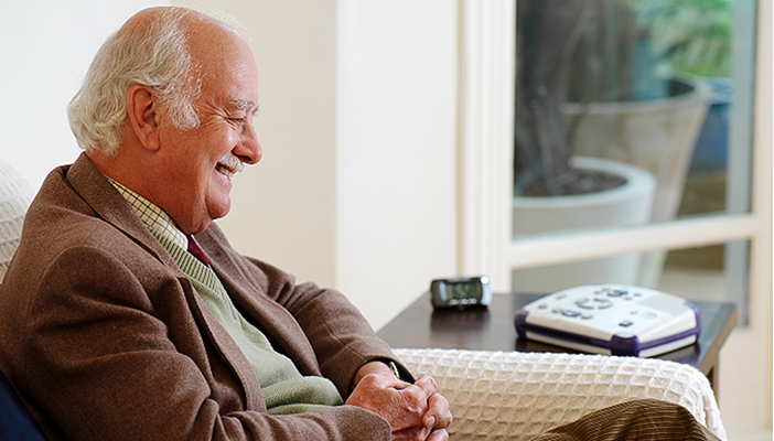 Image of a smiling man sitting on his sofa