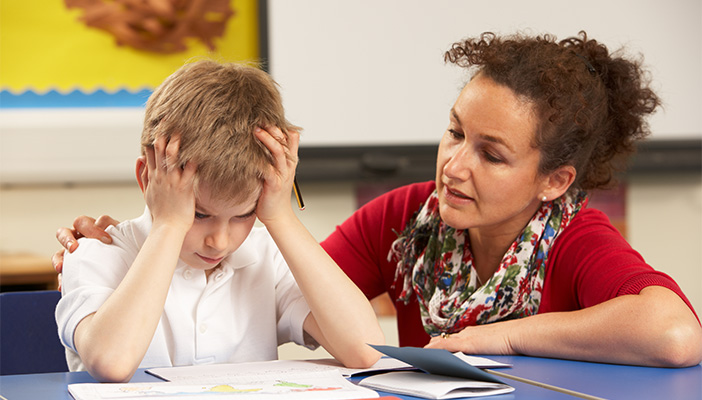 Image shows a young boy at school sat next to his teacher in a classroom with work in front of them. The boys hands are placed against his head reflecting his frustration.
