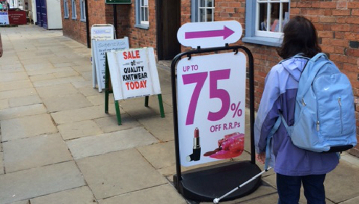 Image shows advertising boards lining high street.