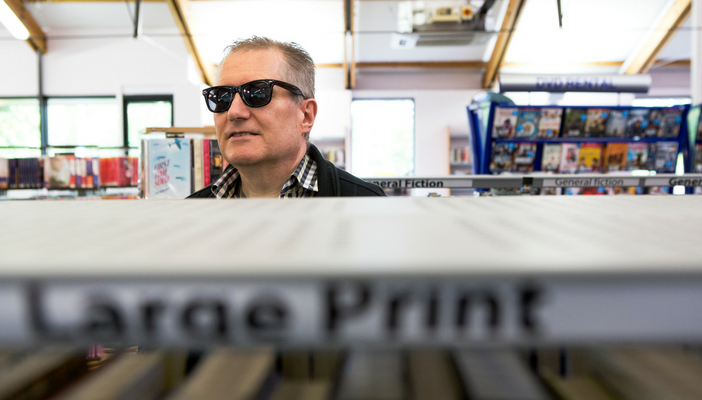 Man with sunglasses on stands behind a section of books labelled large print