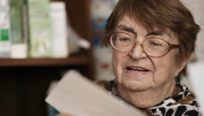 An elderly lady reading something on a piece of paper