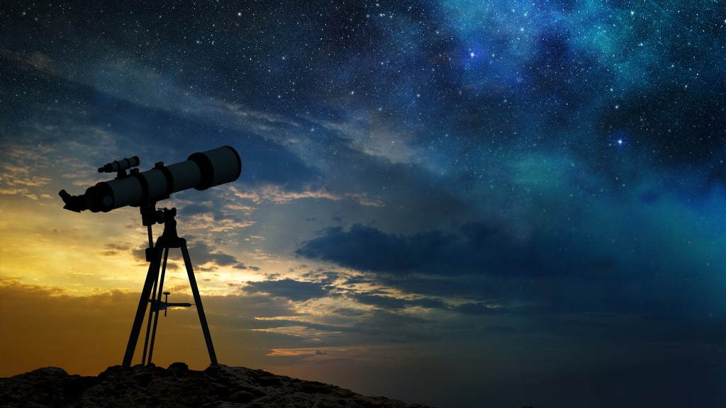 A telescope sits on elevated ground pointed up into the night sky