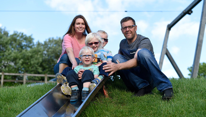 Image shows a man and a woman with three young kids who are going down a slide at a park.