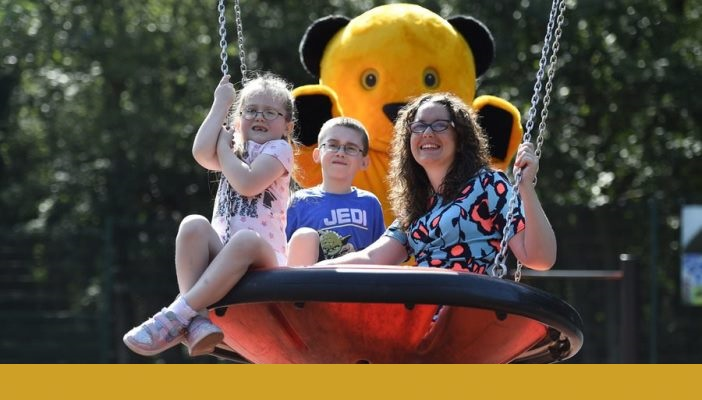 Andrea sat on a big swing in the park with two kids and someone dressed as Sooty standing in the back