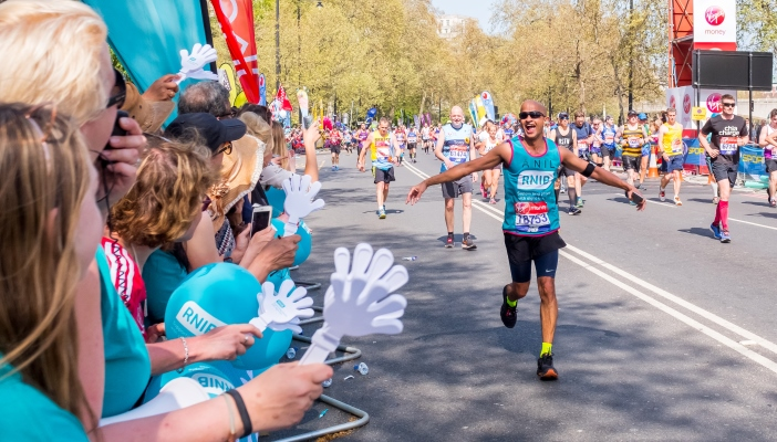 Anil D'Souza with arms outstretched looking thrilled as he calls out to cheerers at mile 25.jpg
