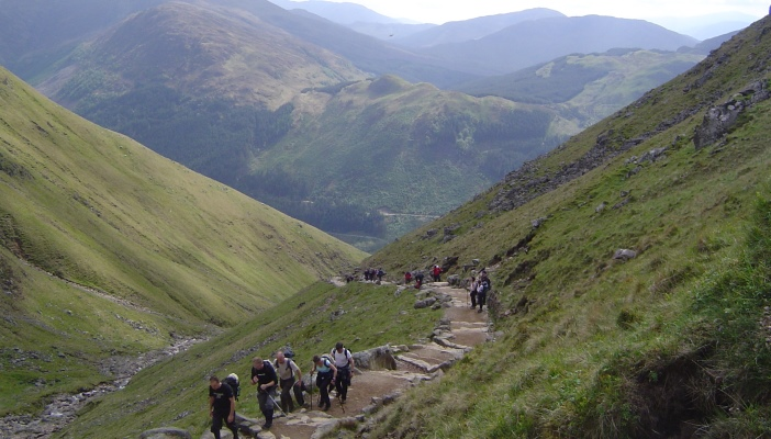 Image shows a group of people trekking with a scenic backdrop of greenery and mountains