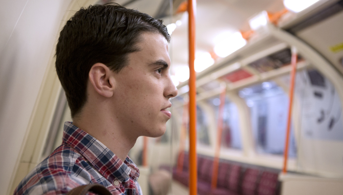 Side profile of a man sat on the London Underground