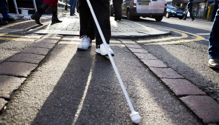 Image shows white cane user on street