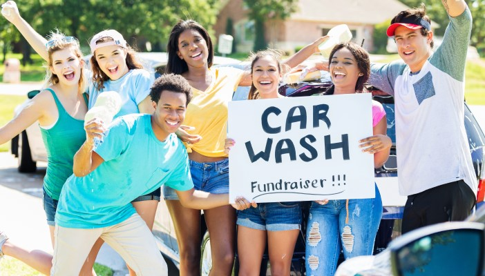 "A group of people in front of a car holding a sign that says ""Car Wash fundraiser"""