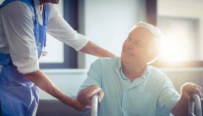 Care home staff member assisting patient