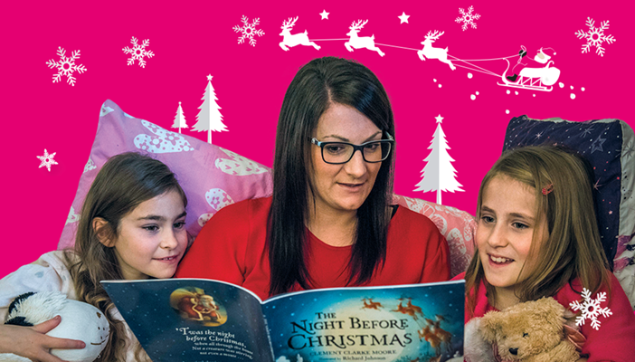 Carolyn reading to her two daughters in bed against a Christmassy backdrop