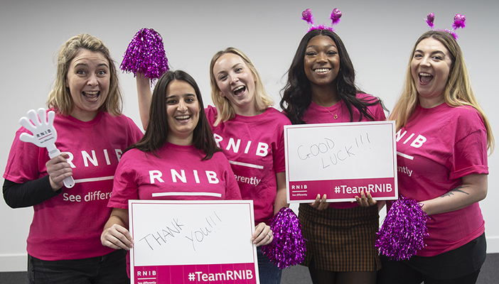 RNIB Challenge Events team holding signs and wearing RNIB t-shirts