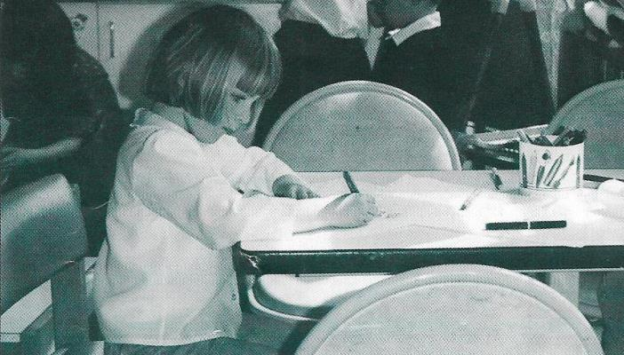 Black and white photo of girl with nystagmus at school desk