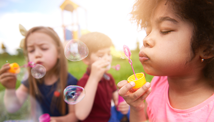 Children blow bubbles together on a sunny day