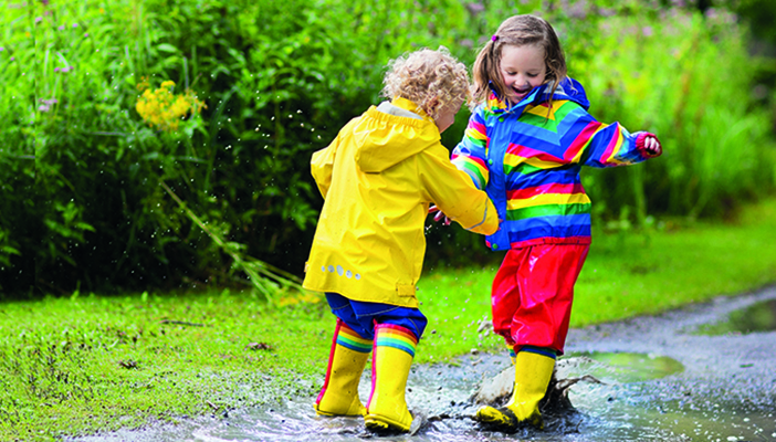 Two children in waterproofs and wellies play in a puddle