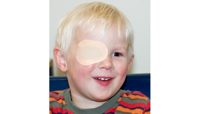 Young boy with his right eye covered for occlusion therapy
