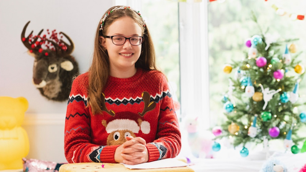 11 year old Keira wearing a Christmas jumper with a decorated Christmas tree in background for RNIB's 2020 Christmas appeal