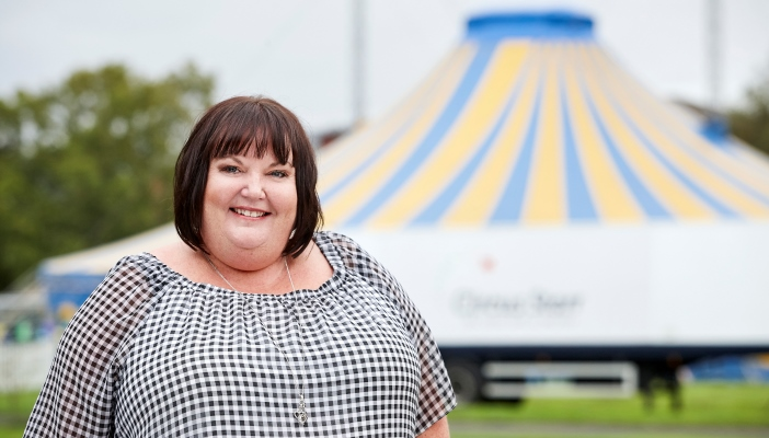 Image shows Jo smiling with a circus tent in the background
