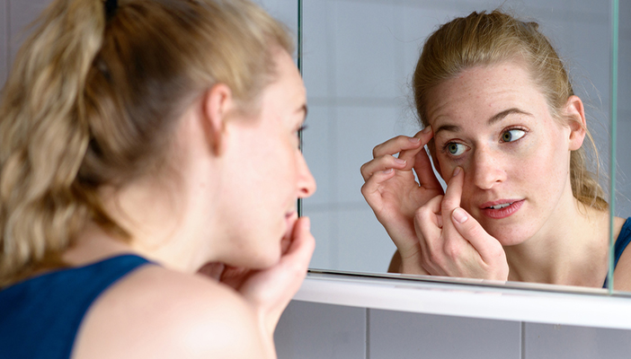 Reflection of woman looking in mirror and putting in contact lens