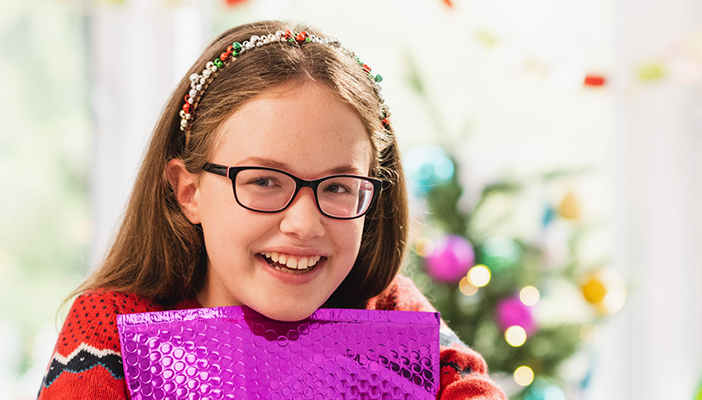 Christmas appeal - Keira hugs a purple envelope containing her braille letter from Santa