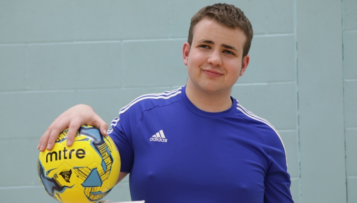 Jake holding a football and wearing sports gear
